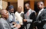 District Commissioner of Eldoret Christopher Wanjau and County Secretary Phillip Arap Meli receive DVD copies of 'An African Answer' from Pastor James Wuye and Imam Muhammad Ashafa. Joseph Wainaina is third from left.